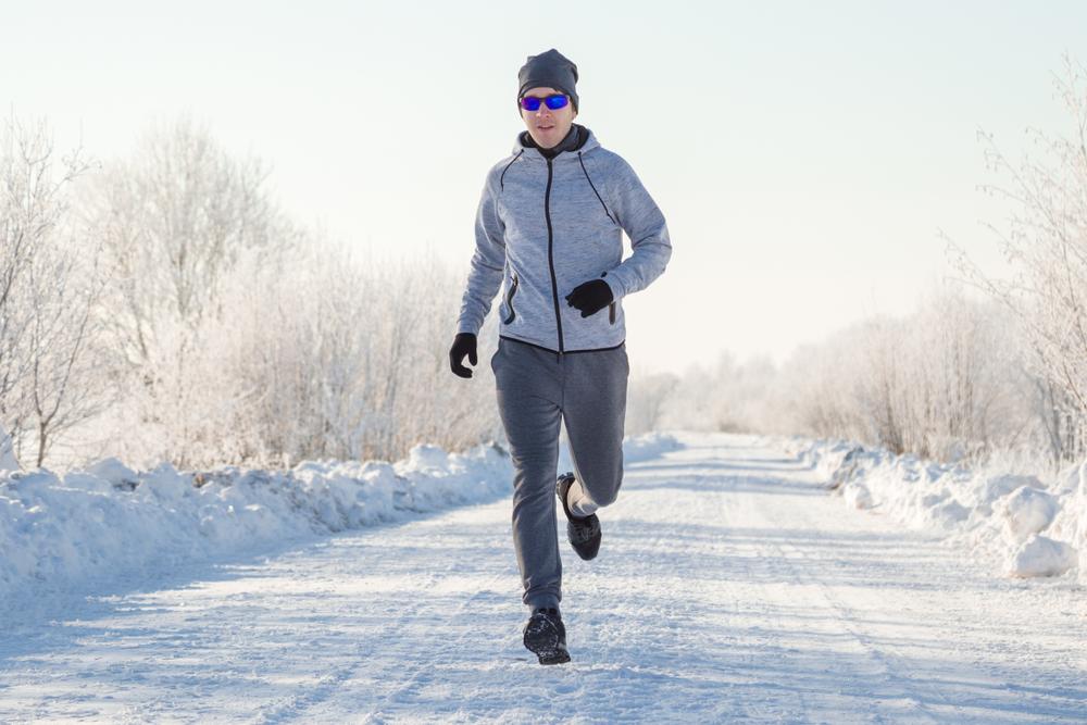 Man in sunglasses running on snowy road